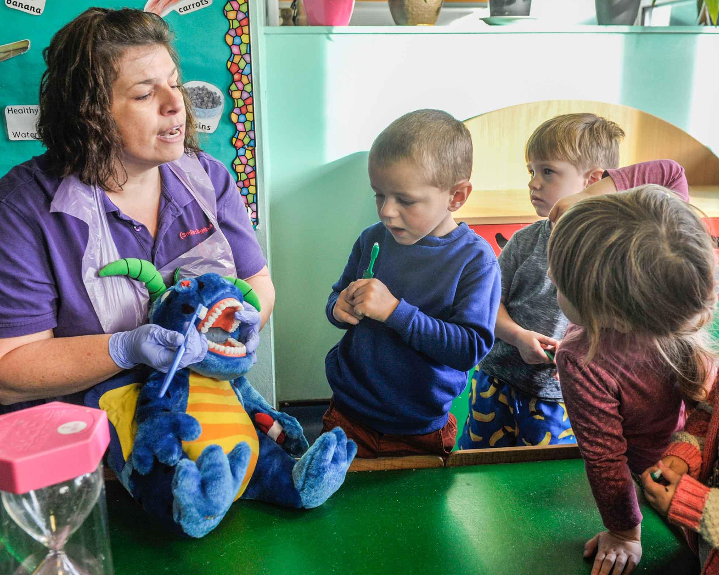 Brighter Smiles dental nurse showing children how to brush dragon's teeth